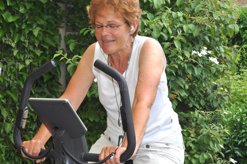 Ältere Frau, die Musik während des Trainings hört lizenzfreie stockfotografie