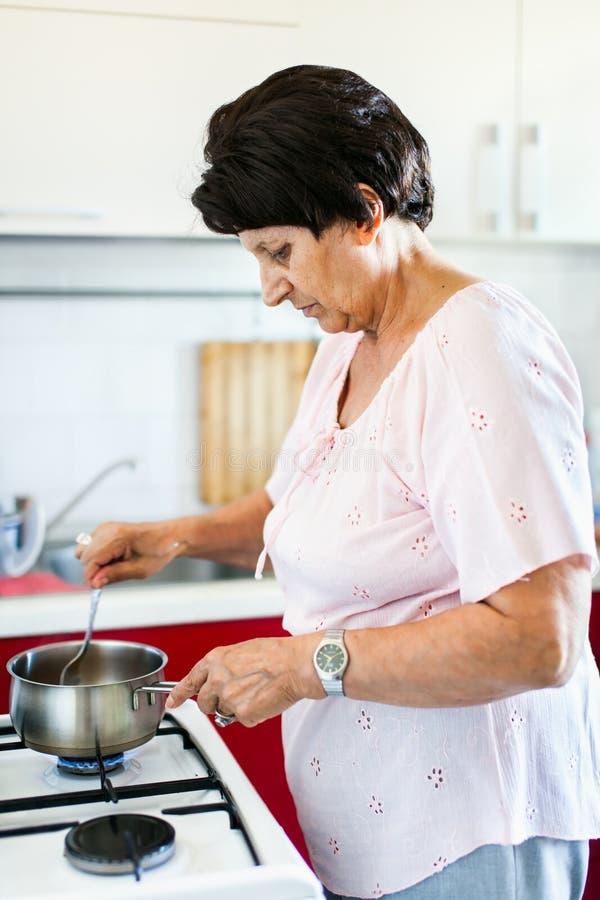 Ältere Frau, die Nahrung zubereitet lizenzfreies stockfoto