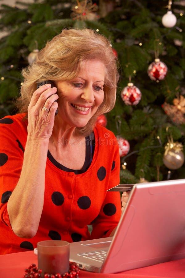 Ältere Frau, die online für Weihnachtsgeschenke kauft lizenzfreies stockfoto