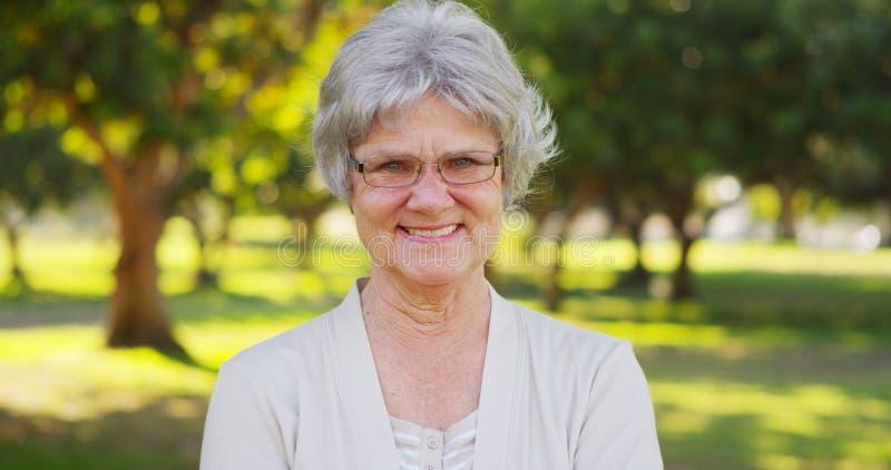 Ältere Frau, die am Park lächelt lizenzfreie stockbilder