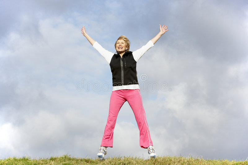 Ältere Frau, die in Park springt stockfotos