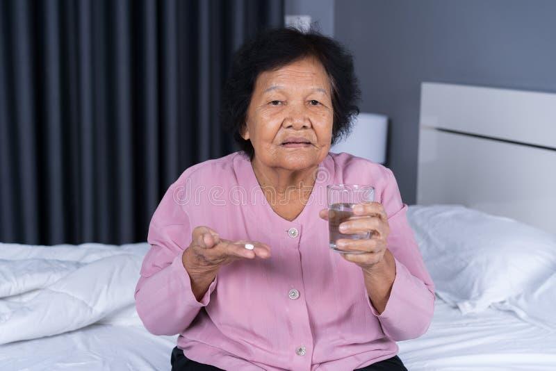Ältere Frau, die Pille mit Glas Wasser im Bett einnimmt stockfotografie