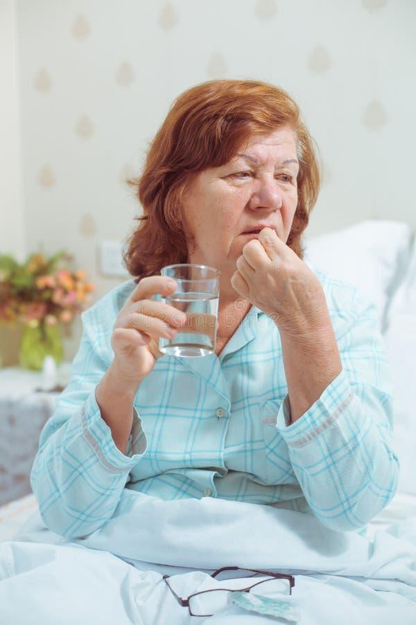 Ältere Frau, die Pille nimmt stockfotografie