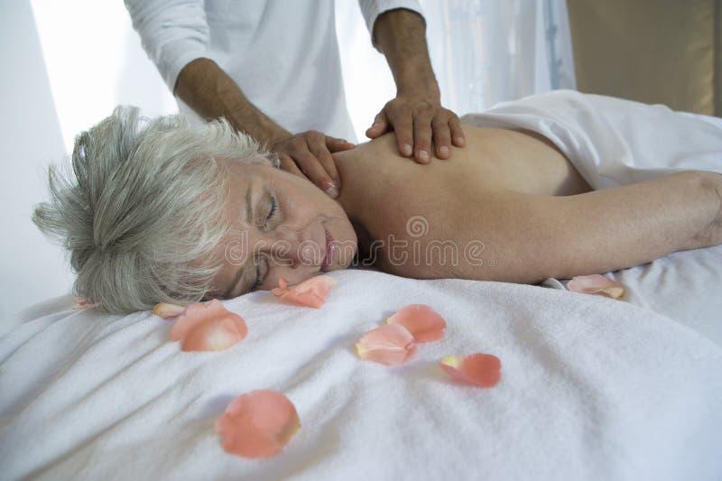 Ältere Frau, die Rückenmassage empfängt stockfotografie