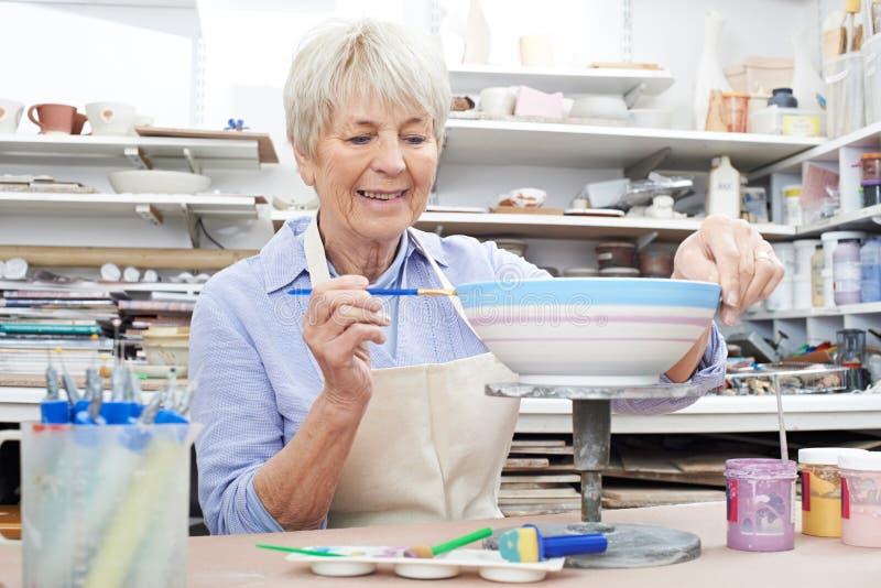 Ältere Frau, die Schüssel in der Tonwaren-Klasse verziert stockfotografie