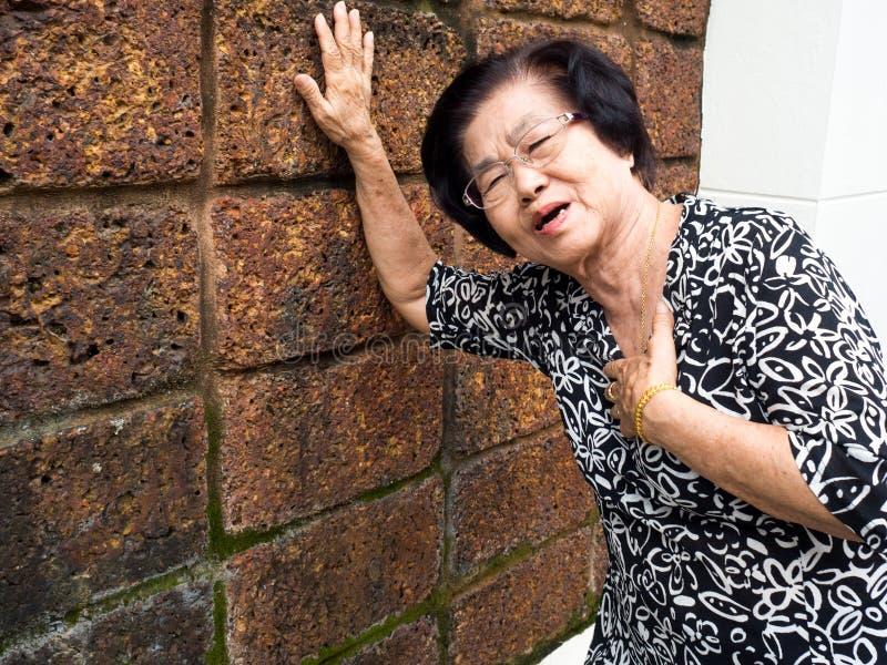 Ältere Frau, die Schmerz in der Brust und ihre haltene Brust wegen der Herzinfarktbildung hat Herzinfarkt-Konzept lizenzfreies stockfoto