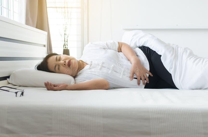 Ältere Frau, die schmerzliche Magenschmerzen zu Hause, älteres weibliches Leiden von den Bauchschmerzen im Schlafzimmer hat lizenzfreies stockbild