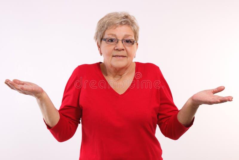 Ältere Frau, die Schultern zuckt und oben ihre Hände, Gefühle im hohen Alter wirft stockbild