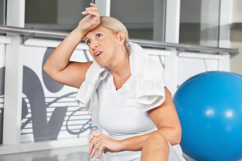 Ältere Frau, die Schweiß von ihr abwischt lizenzfreies stockbild