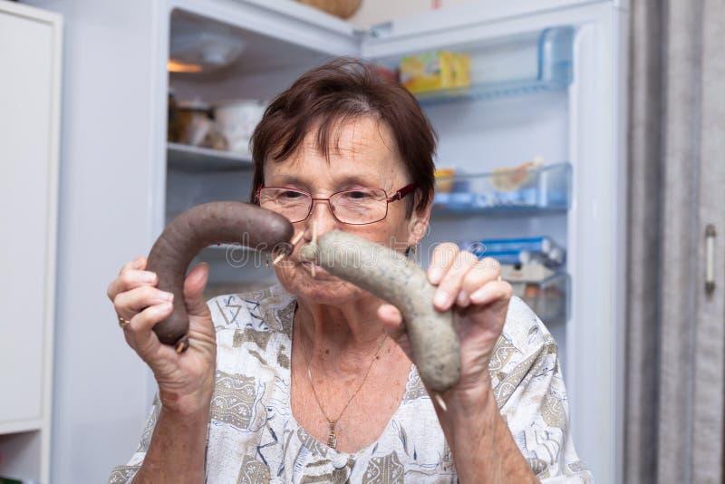 Ältere Frau, die Schweinefleischleberwürste hält stockbilder
