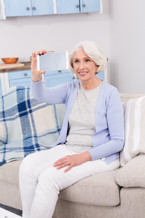 Ältere Frau, die Selbstfotos macht stockbild