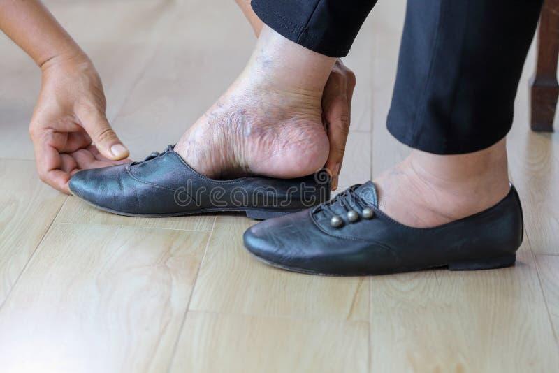 Ältere Frau, die sich sorgfältig auf Geber der Schuhe setzt lizenzfreies stockfoto