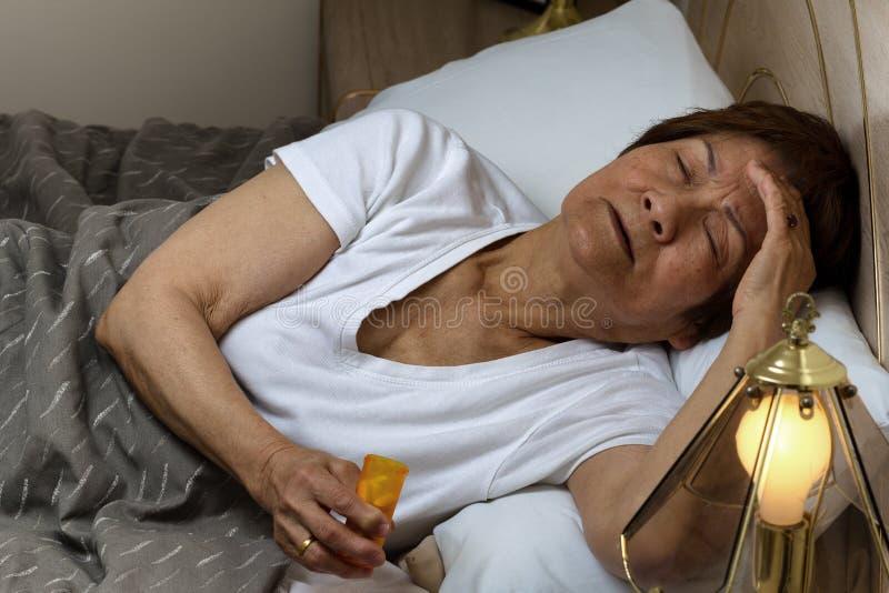 Ältere Frau, die sich vorbereitet, die Medizin wegen des inso in der Nacht einzunehmen stockfoto