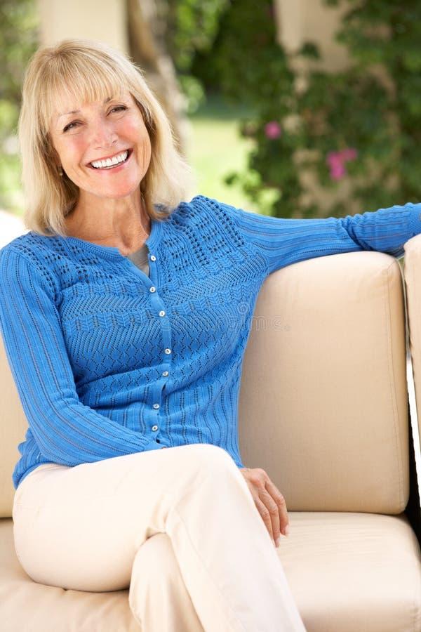 Ältere Frau, die sich zu Hause auf Sofa entspannt stockbild