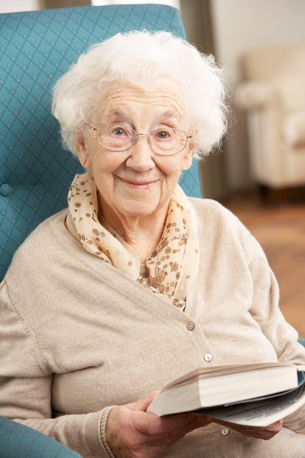 Ältere Frau, die sich zu Hause im Stuhl entspannt stockfotografie