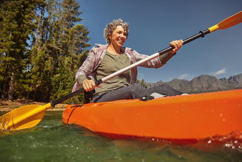 Ältere Frau, die am Sommertag canoeing ist stockfotos