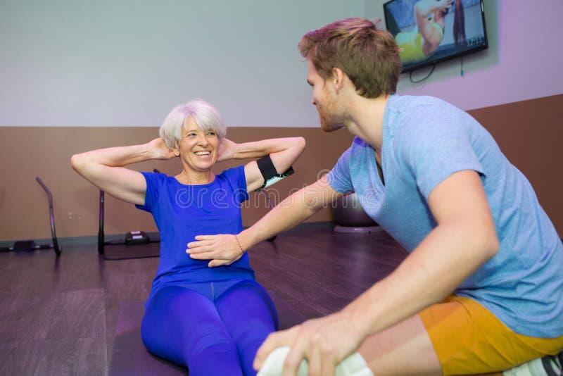 Ältere Frau, die Sportübungen mit Trainer tut lizenzfreies stockbild