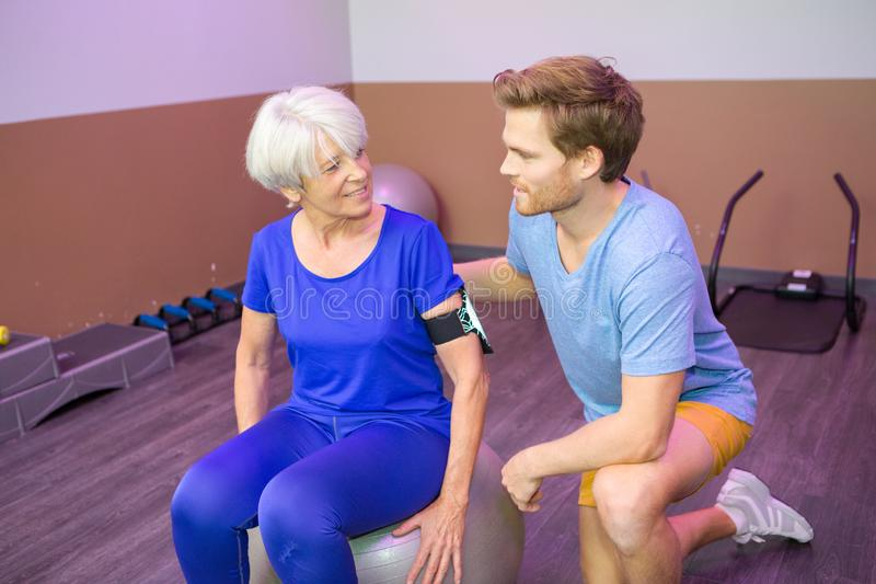 Ältere Frau, die Sportübungen mit Trainer tut stockbild
