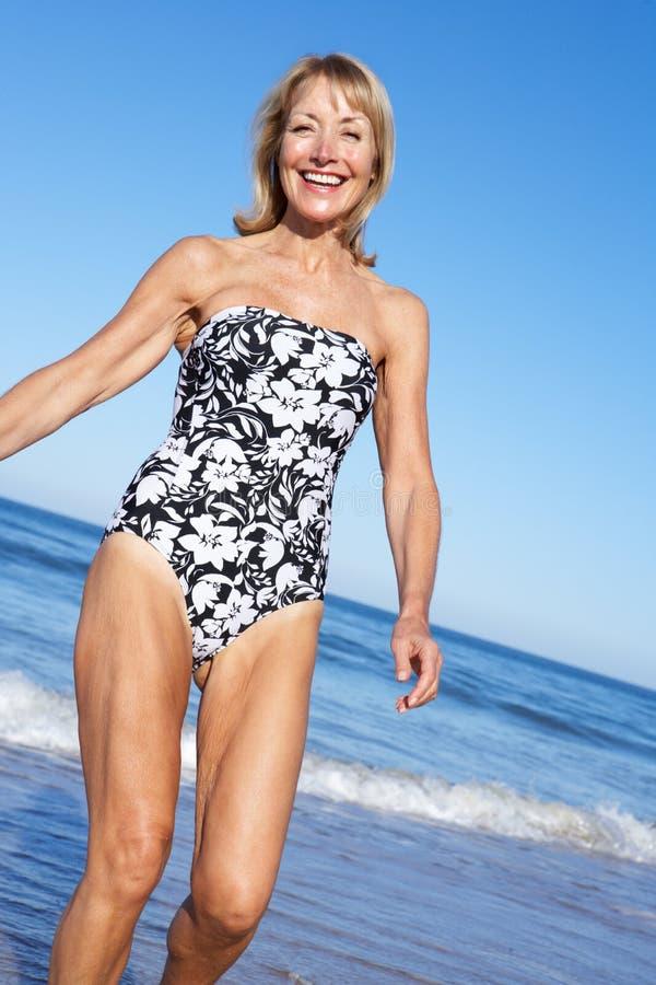 Ältere Frau, die Strand-Feiertag genießt stockfoto