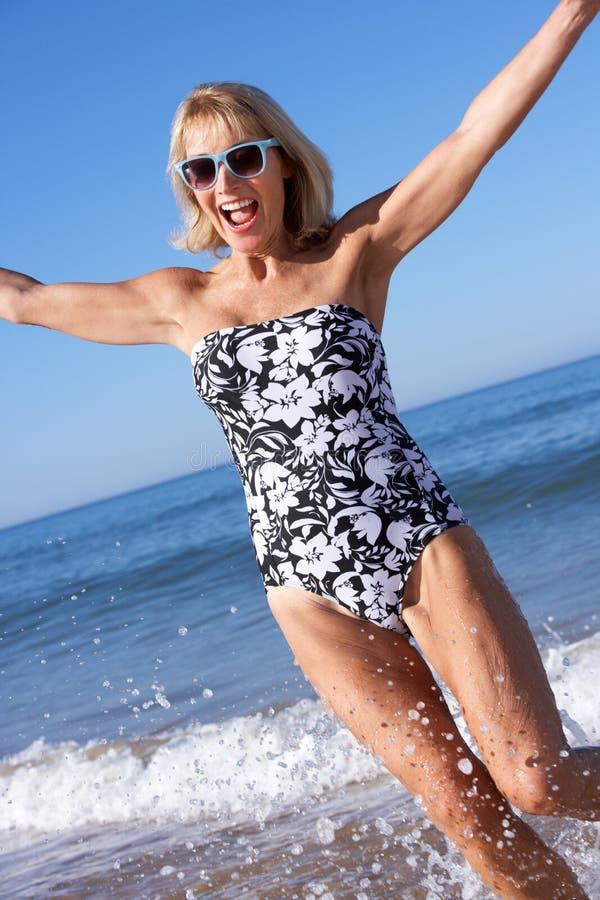 Ältere Frau, die Strand-Feiertag genießt stockfotografie