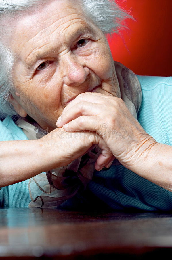 Ältere Frau, die am ta sitzt stockbild