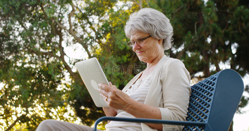 Ältere Frau, die Tablette am Park verwendet stockbild