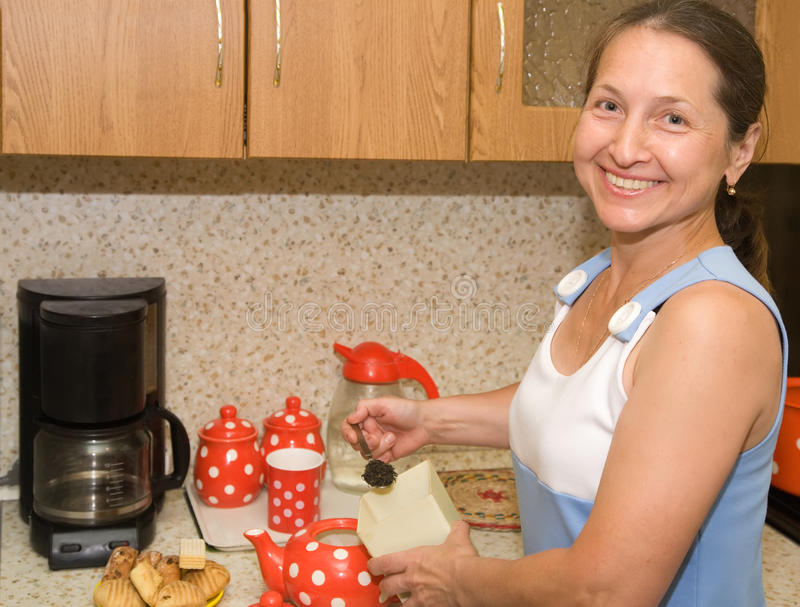 Ältere Frau, die Tee bildet stockfotografie