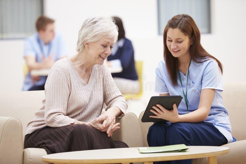 Ältere Frau, die Testergebnisse mit Krankenschwester bespricht lizenzfreies stockbild