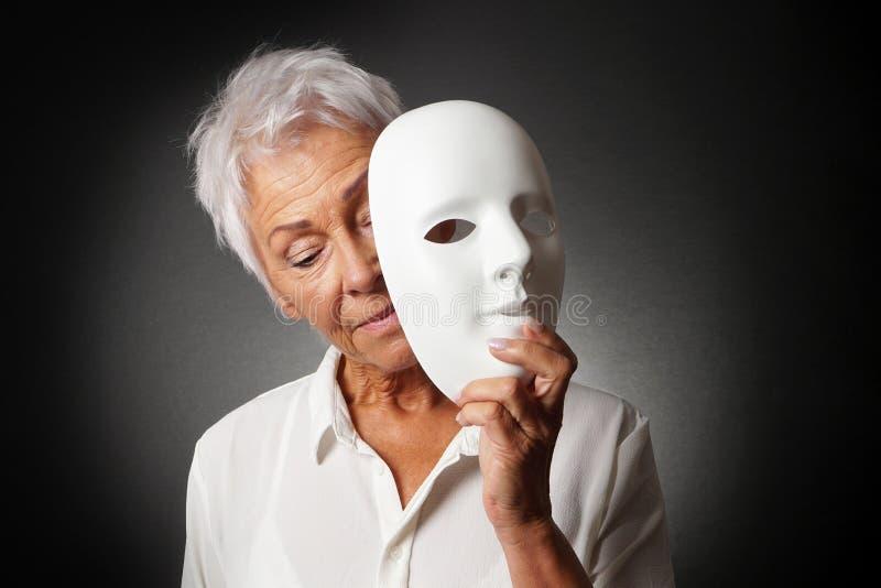 Ältere Frau, die trauriges Gesicht hinter Maske versteckt lizenzfreie stockbilder