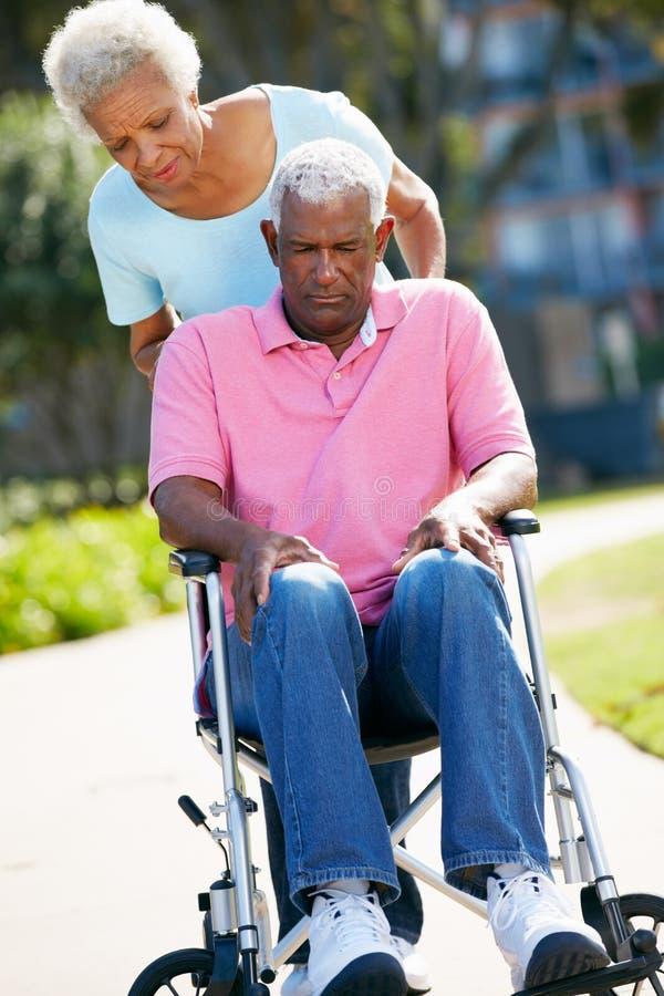 Ältere Frau, die unglücklichen Ehemann im Rollstuhl drückt lizenzfreies stockfoto