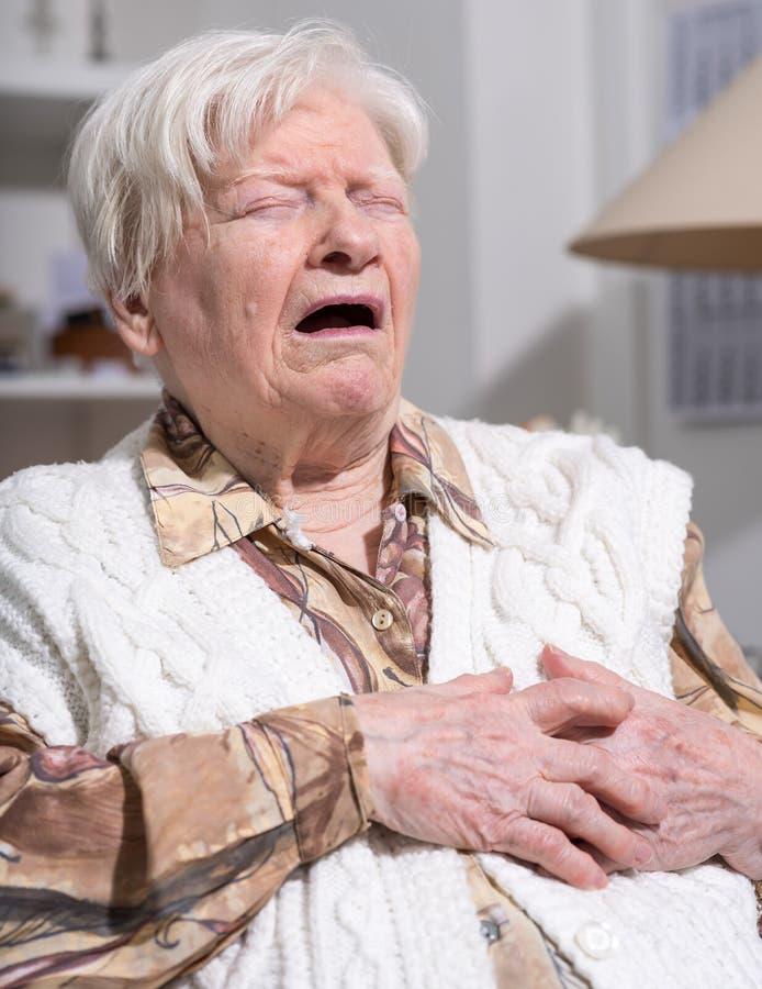 Ältere Frau, die unter Herzinfarkt leidet lizenzfreie stockfotos