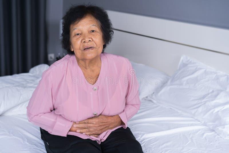Ältere Frau, die unter Magenschmerzen auf Bett leidet stockfoto
