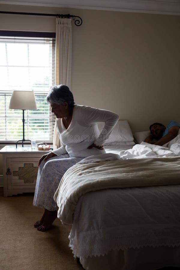 Ältere Frau, Die Unter Rückenschmerzen Beim Sitzen Auf Bett Leidet ...