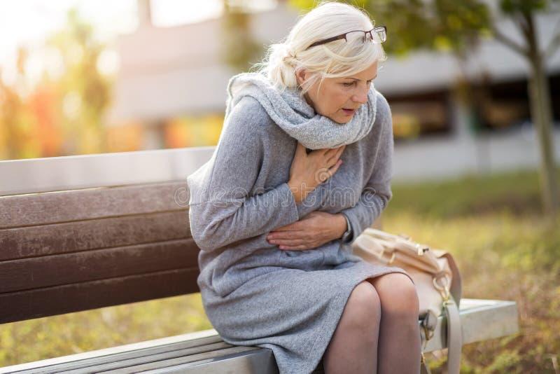 Ältere Frau, die unter Schmerz in der Brust leidet lizenzfreie stockfotos