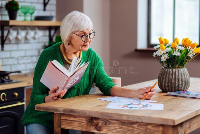 Ältere Frau, die versucht, vedic Diagramme unter Verwendung des Buches zu verstehen lizenzfreie stockbilder