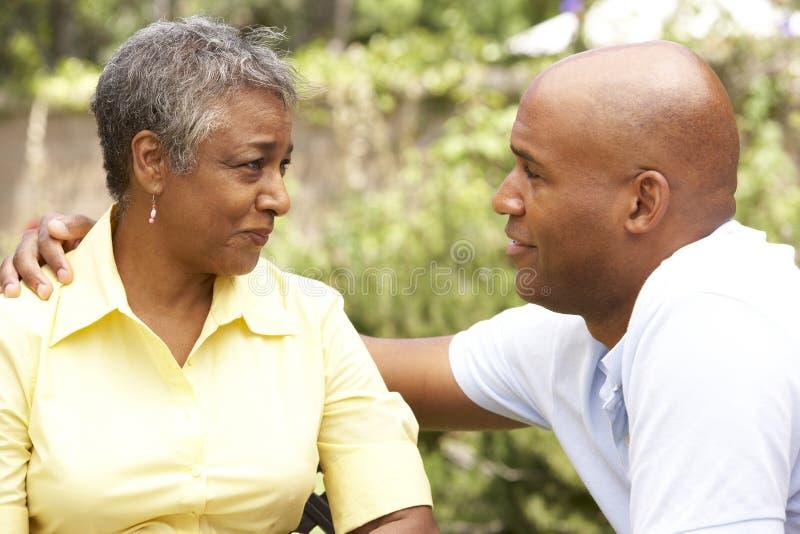 Ältere Frau, die von Adult Son getröstet wird lizenzfreies stockbild