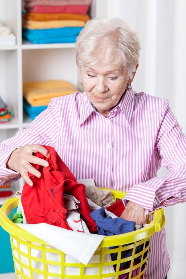 Ältere Frau, die Wäscherei tut stockbild