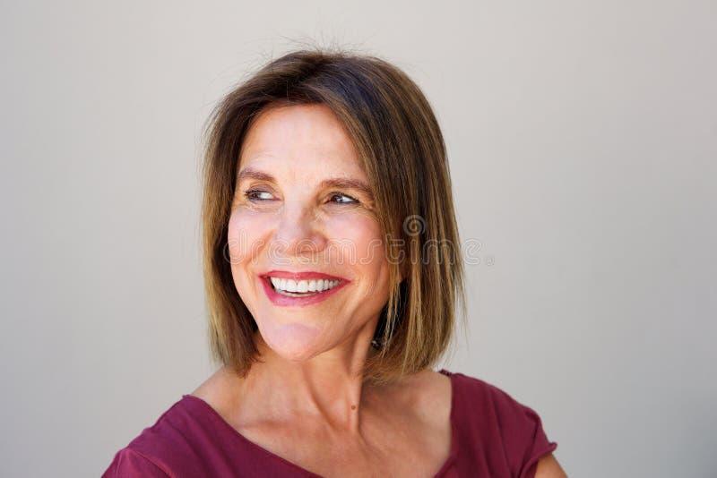 Ältere Frau, die weg lacht und schaut stockfoto