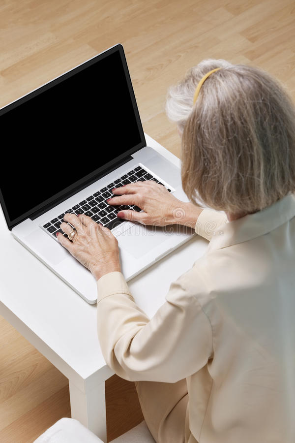 Ältere Frau, die zu Hause das Netz auf Laptop surft stockfotografie