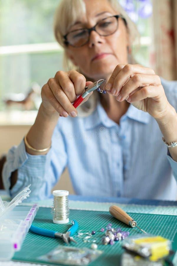 ?ltere Frau, die zu Hause Schmuck-Ohrringe herstellt lizenzfreies stockbild