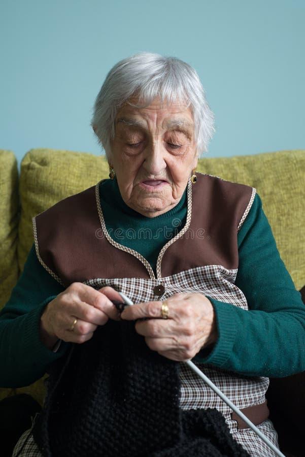 Ältere Frau, die zu Hause strickt stockbilder