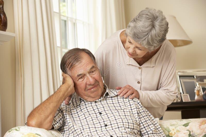 Ältere Frau, die zu Hause unglücklichen Ehemann tröstet stockfoto