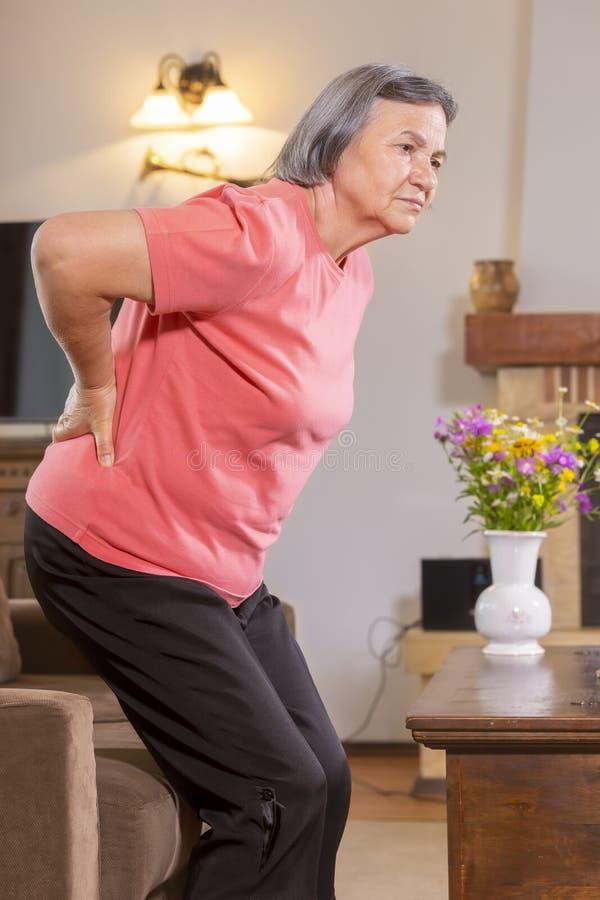 Ältere Frau, die zu Hause unter Rückenschmerzen leidet stockfotografie