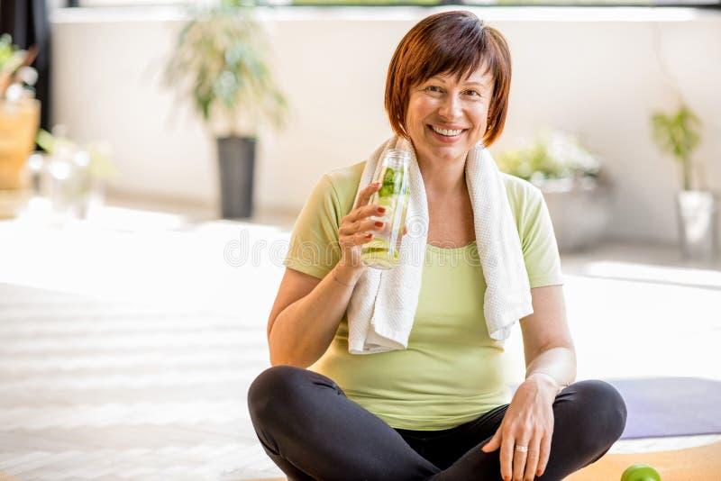 Ältere Frau, die zuhause Yoga tut lizenzfreie stockbilder