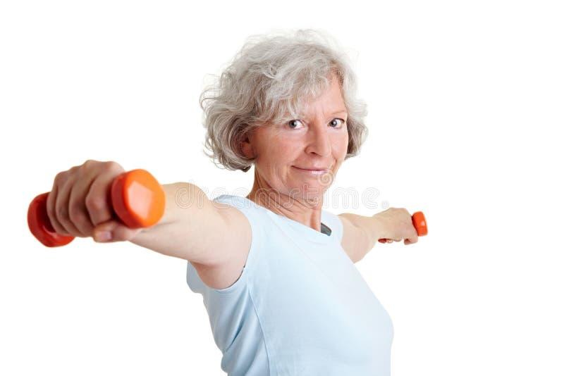 Ältere Frau, die zwei Dumbbells anhält stockfotos