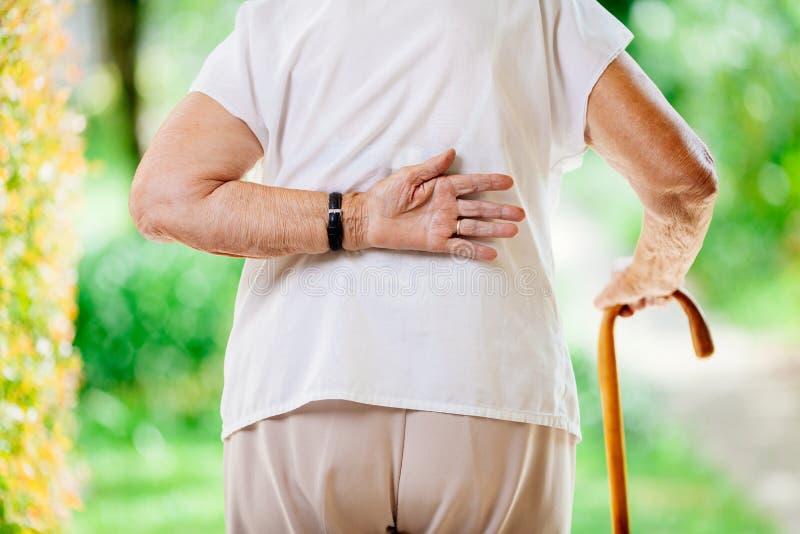 Ältere Frau draußen mit Rückenschmerzen lizenzfreie stockfotos