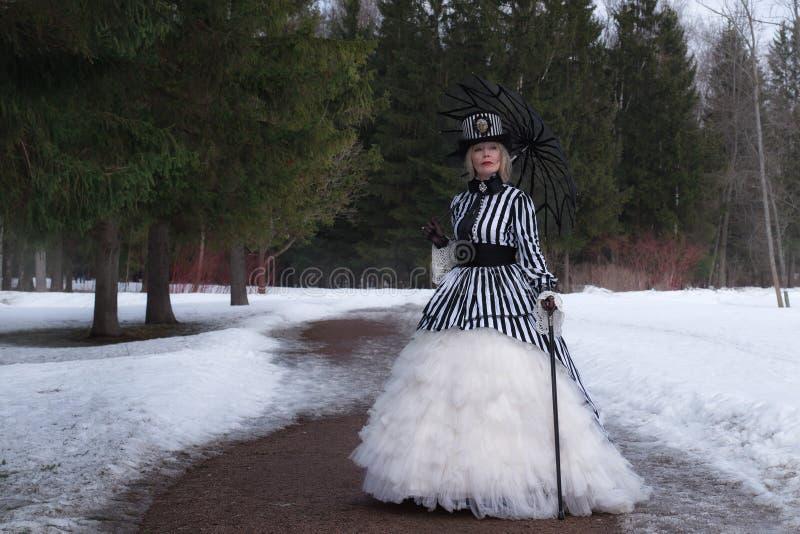 Ältere Frau in einem gotischen Kleid in einem Hut mit einem schwarzen Regenschirm auf Natur im Winter stockbild