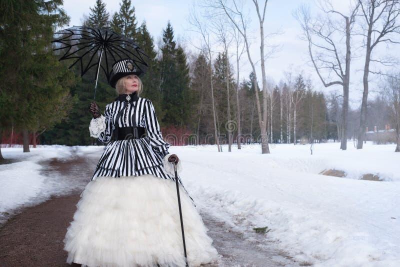 Ältere Frau in einem gotischen Kleid in einem Hut mit einem schwarzen Regenschirm auf Natur im Winter lizenzfreies stockbild