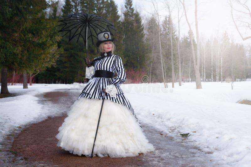 Ältere Frau in einem gotischen Kleid in einem Hut mit einem schwarzen Regenschirm auf Natur im Winter lizenzfreie stockfotografie