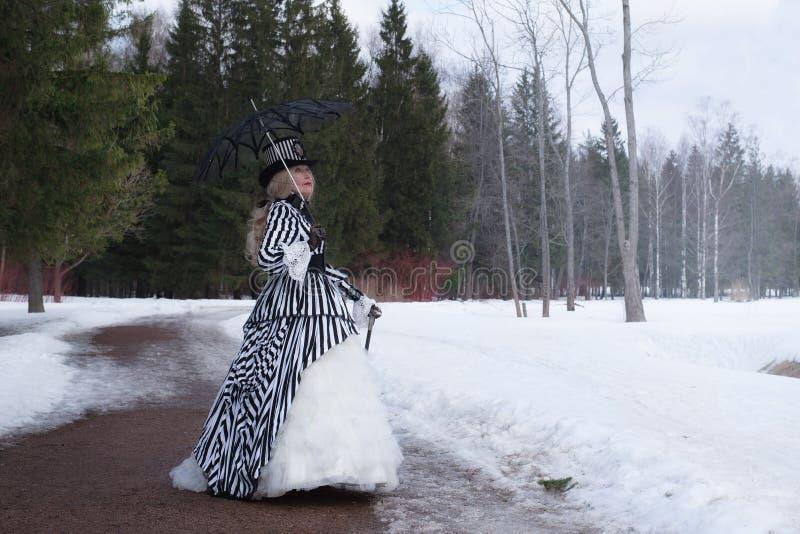 Ältere Frau in einem gotischen Kleid in einem Hut mit einem schwarzen Regenschirm auf Natur im Winter stockfoto